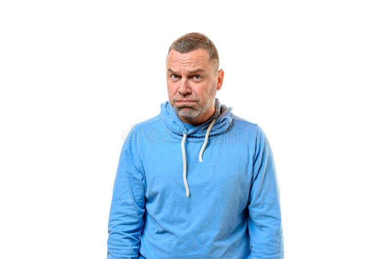 Knorrige mens in blauwe sweater dichtbij witte muur stock foto