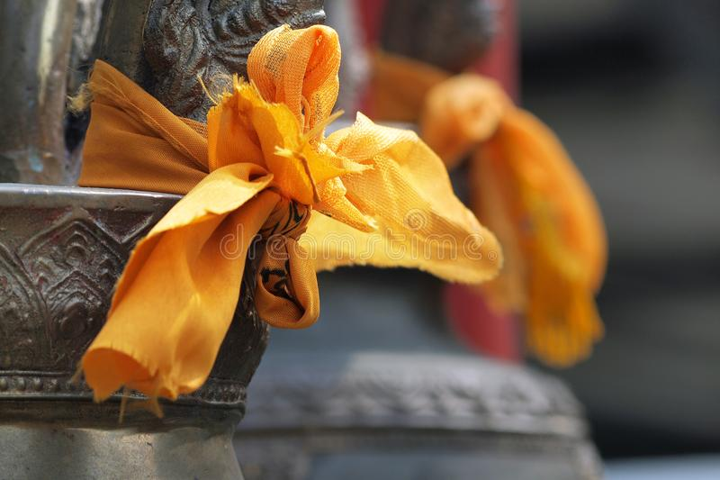 Knot on bell. Knot of orange fabric on buddhist bell stock images