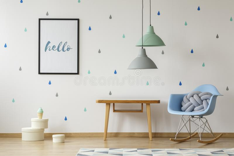 Knot pillow in a baby blue, modern rocking armchair, wooden table and a poster on a wallpaper with colorful droplets in a natural stock images