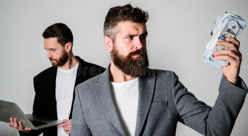 They know how to make money. Team of web developer with laptop and sales manager with cash money. Developing stock photos