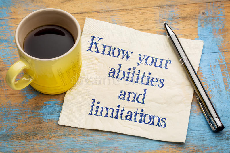 Know your abilities and limitations. Handwriting on a napkin with a cup of espresso coffee royalty free stock image