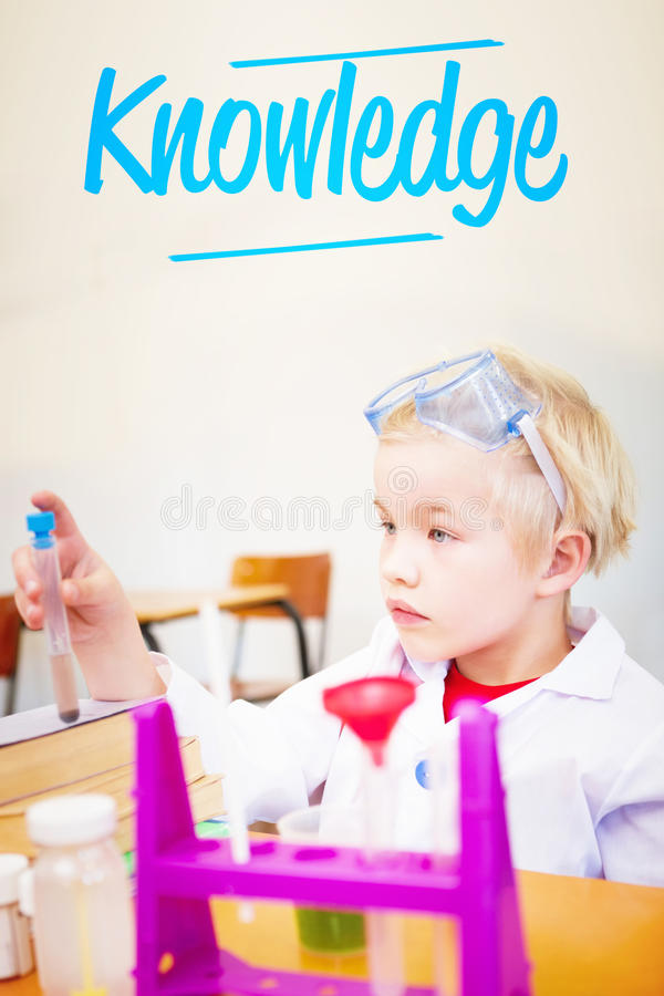 Knowledge against cute pupil dressed up as scientist in classroom stock image