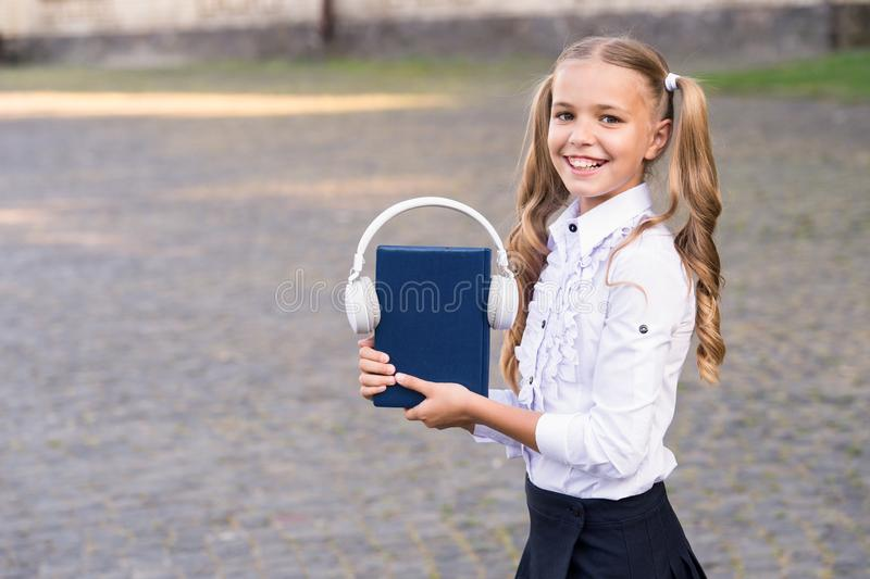 Knowledge assimilate better this way. Audio book concept. Digital technologies for learning. Elearning and modern. Methods. Girl cute schoolgirl hold book and royalty free stock image