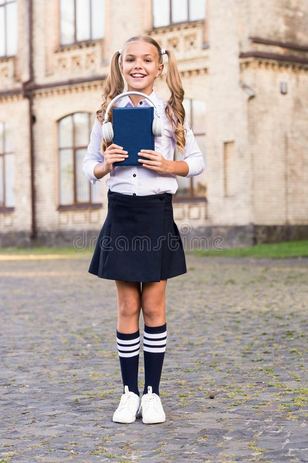 Knowledge assimilate better this way. Audio book concept. Listening school book. Digital technologies for learning. Elearning and modern methods. Girl cute royalty free stock images
