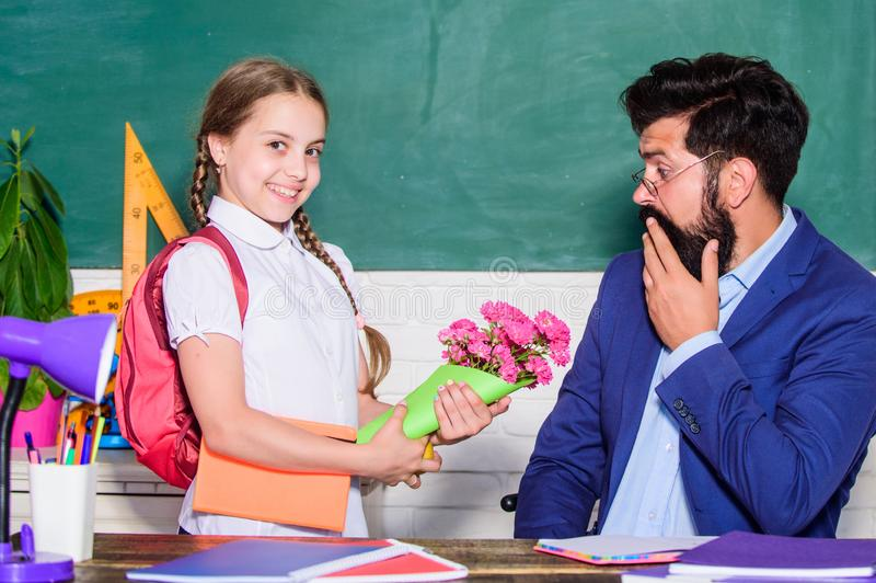 Knowledge day is 1 september. teachers day. Daugghter and father with flowers. small school girl kid with flower bouquet. Flower present for best teacher. back royalty free stock photo