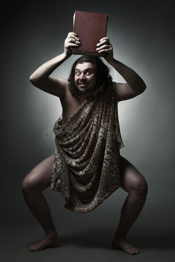 Knowledge is power. Caveman wearing leopard skin hold big book over head royalty free stock photos