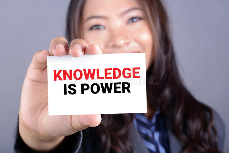 KNOWLEDGE IS POWER message on the card shown by a woman royalty free stock photos