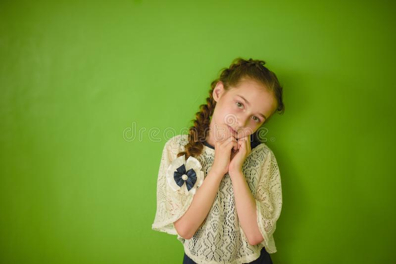 Knowledge is always yours. Small schoolgirl in uniform clothes against green background royalty free stock photography
