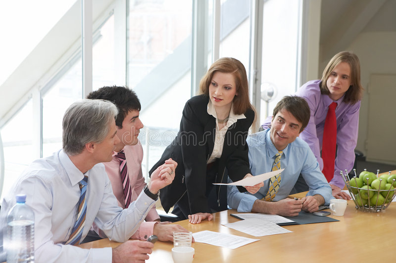 She knows. Five businesspeople are discussing something on a meeting