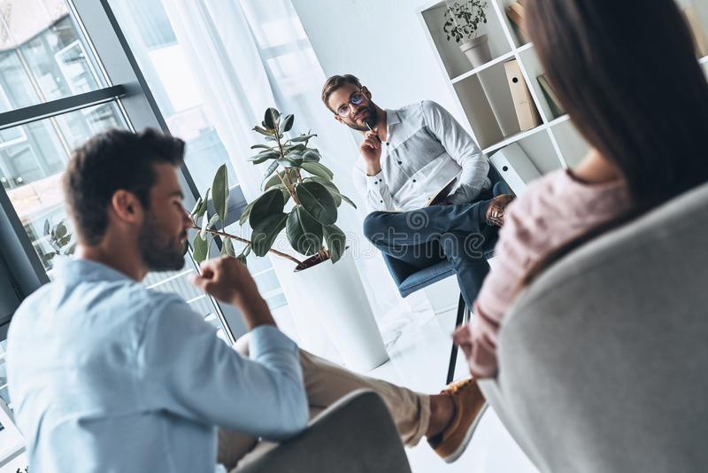 He knows exactly what to say. Young married couple talking while sitting on the therapy session with psychologist stock images