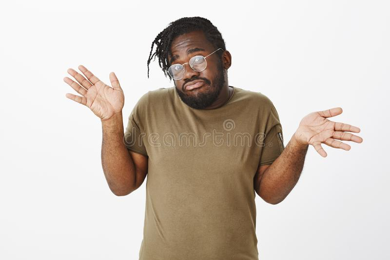 He knows nothing. Portrait of unaware clueless cute african-american brother in olive t-shirt and glasses, shrugging and stock image