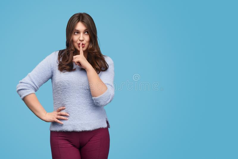 Knubbig kvinna som håller hemlighet arkivbild