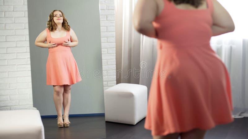 Knubbig stilfull ung dam som ser hennes reflexion som tillfredsställs med den curvy kroppen royaltyfria foton