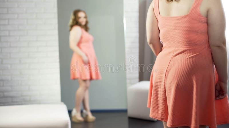 Knubbigt kvinnligt stående framme av spegeln och att se hennes plus-format utseende arkivfoto