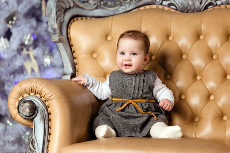 Knubbigt litet gulligt behandla som ett barn flickasammanträde i en beige stol och smilin arkivfoton