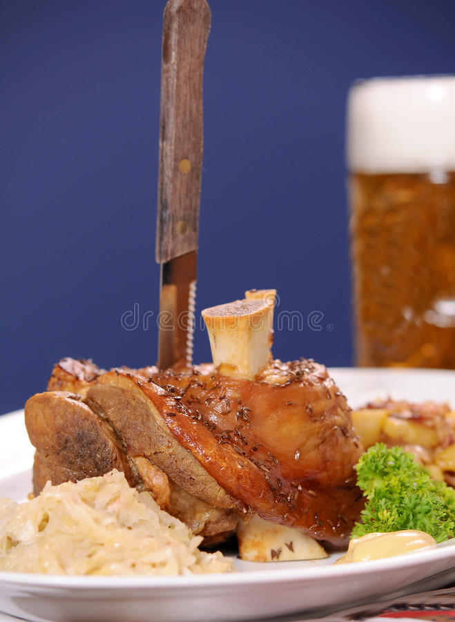 Knuckle of pork. Cutting the knuckle of pork royalty free stock photos