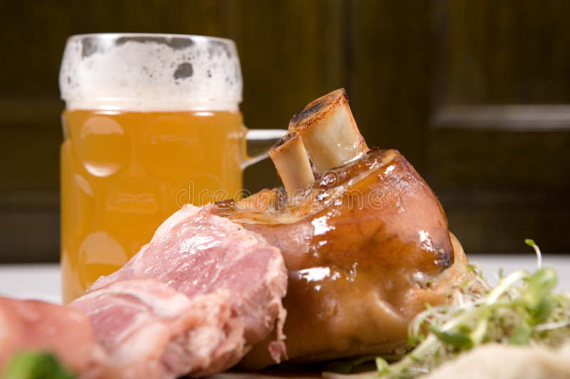 Knuckle of pork. A wider view of knuckle of pork with a glass of beer royalty free stock photos