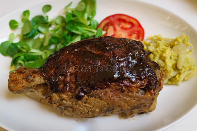 Knuckle of traditional italian baked pork leg with vegetable, to royalty free stock images
