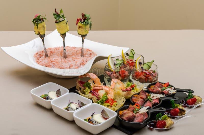 Knuffa omkring tabellen med aptitretare i en restaurang med krudite, guacamel, ceviche, bluefinen, kaviaren, räkor och getost arkivbild