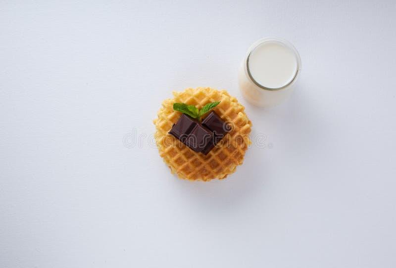 Knusperige belgische Waffeln mit Schokoladensplittern auf einer weißen strukturierten Oberfläche Kleiner Glaskrug mit Milch stockbilder