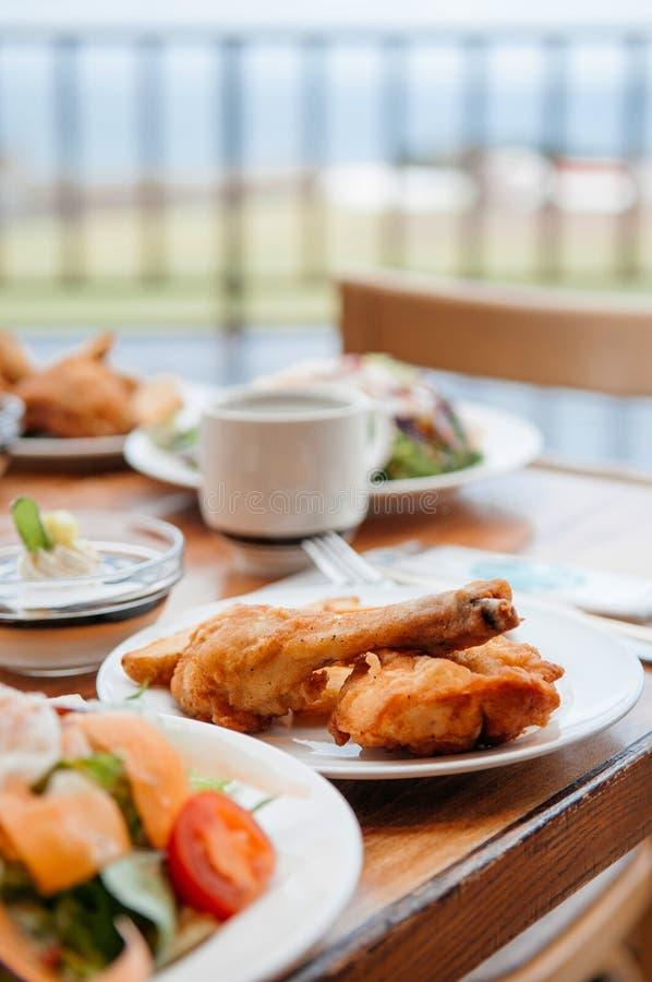 Knusperige frittierte Hühnertrommelbeine und -salat auf Abendtische, c stockfotos