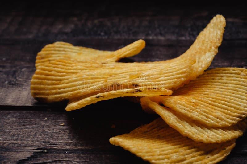 Knusperige Kartoffelchips auf h?lzernem Hintergrund Chips begannen lizenzfreie stockfotografie