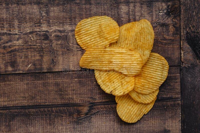 Knusperige Kartoffelchips auf h?lzernem Hintergrund Chips begannen stockbilder