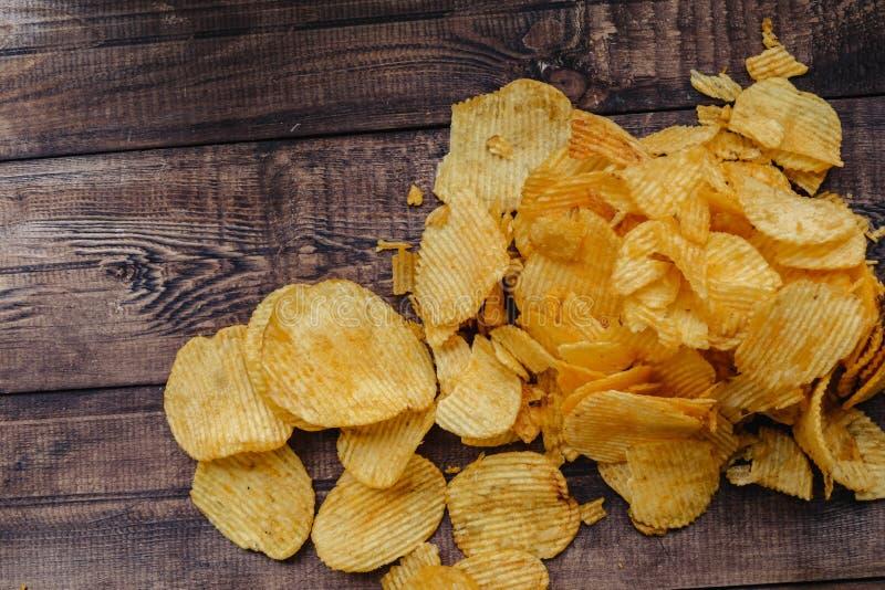 Knusperige Kartoffelchips auf h?lzernem Hintergrund Chips begannen lizenzfreies stockfoto