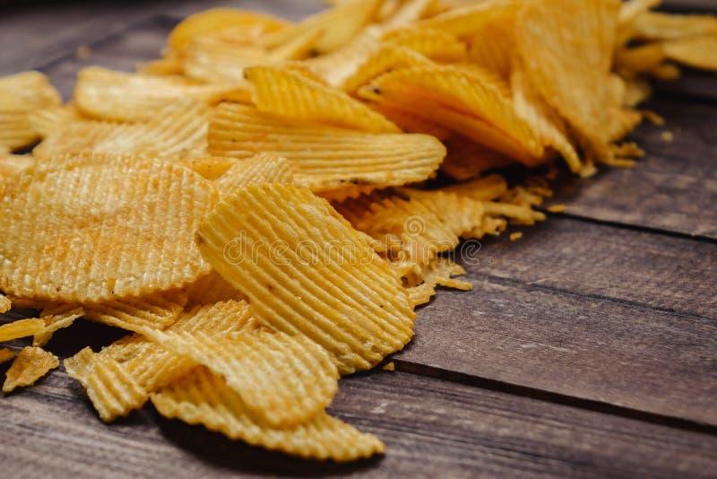 Knusperige Kartoffelchips auf h?lzernem Hintergrund Chips begannen lizenzfreies stockbild