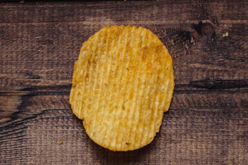 Knusperige Kartoffelchips auf h?lzernem Hintergrund Chips begannen stockfoto