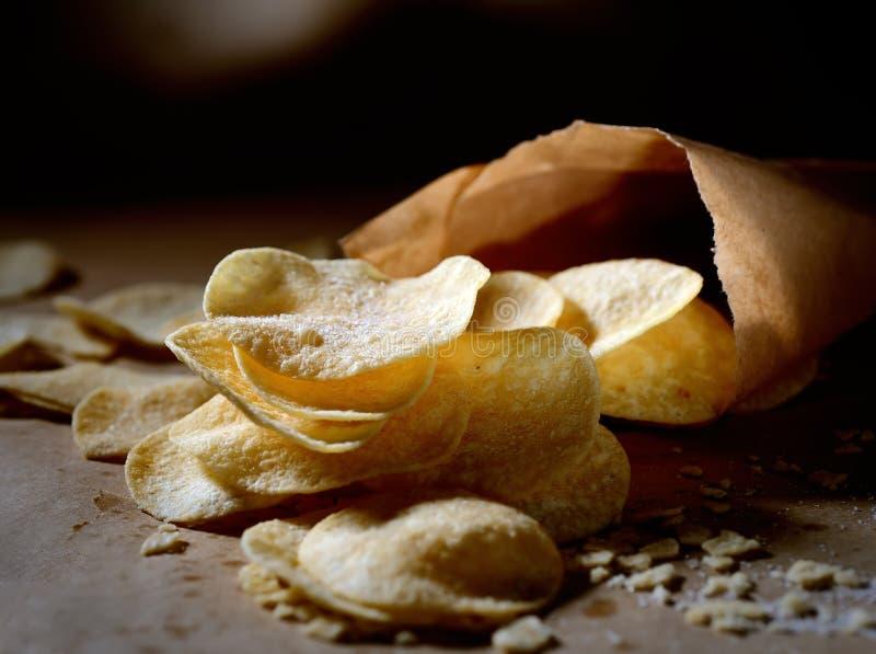 Knusperige Kartoffelchips in den Papiertüten auf einem dunklen Hintergrund lizenzfreies stockfoto