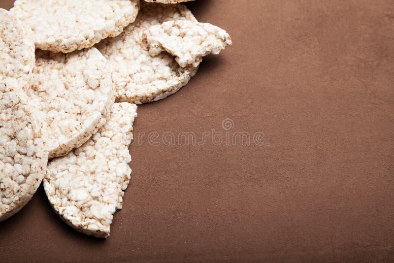Knusperige Kekse des vegetarischen Reises auf einem braunen Weinlesehintergrund, leerer Raum für Text stockbild