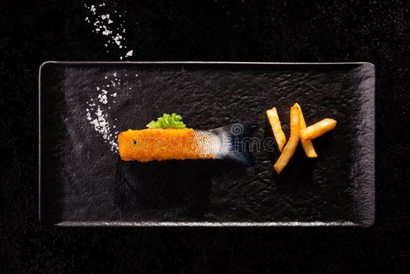 Knusperiges frittiertes Fischstäbchen mit rohem Endstück und Salz als Blasen lizenzfreie stockbilder