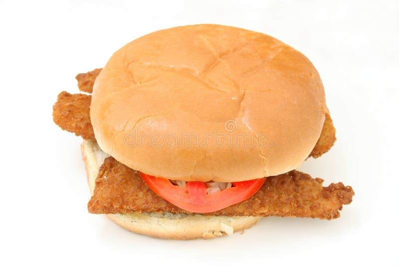 Knusperiges gebratenes Fisch-Sandwich mit Tomate und gewürfelter Zwiebel stockfotografie