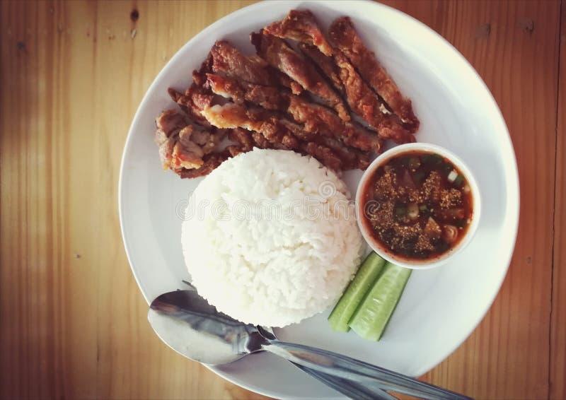 Knusperiges Schweinefleisch mit Reis und gebürtiger Quelle stockfotos