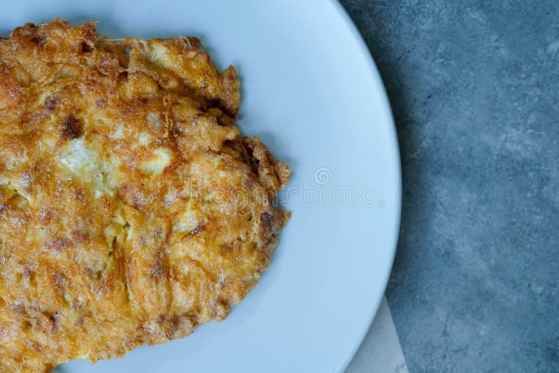 Knusperiges thailändisches Omelettschweinefleisch in der blauen keramischen Platte stockfotos