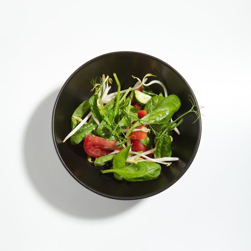 Knusprige Gemüse-Grün-Mischung in der runden schwarzen Schüssel lokalisiert auf Whi lizenzfreies stockbild