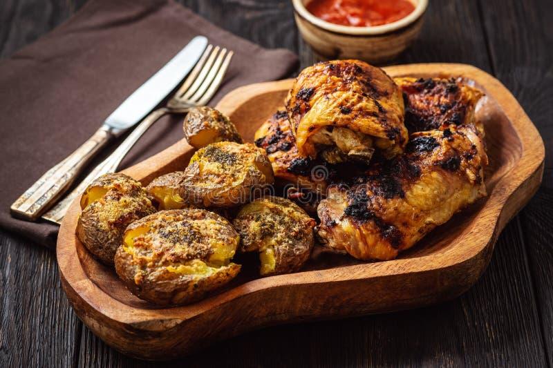 Knusprige Kartoffeln, geröstet mit Knoblauch, Parmesan und gegrilltem Huhn lizenzfreie stockfotos