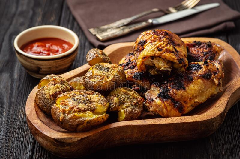 Knusprige Kartoffeln, geröstet mit Knoblauch, Parmesan und gegrilltem Huhn stockfotografie