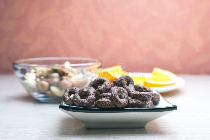 Knusprige Schokoladen-Getreide ringsum Hafer in einem Teller, in einer Glasschüssel Nüssen und in orange Scheiben in einer weißen lizenzfreie stockbilder