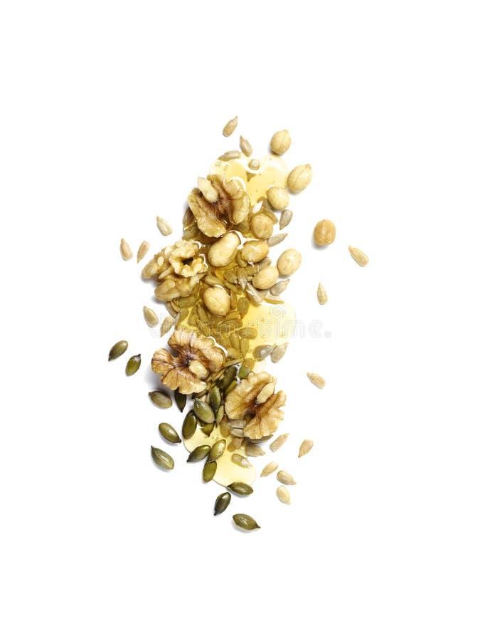 Knuspriger Snack von Nüssen, von pepitas, von Sonnenblumensamen und von Honig auf Weiß lizenzfreies stockbild