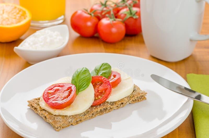 Knuspriges Brot mit Tomate und Mozzarella auf einer Tabelle stockfotografie