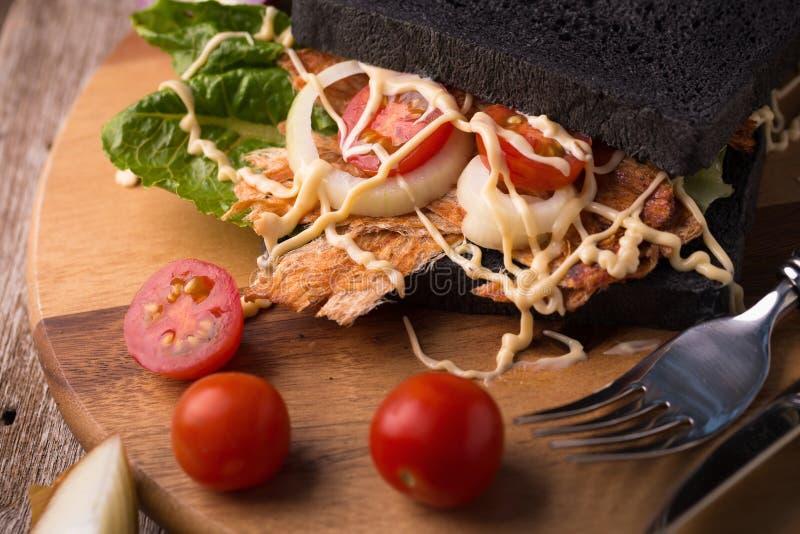 Knyckigt dunkat griskött och grönsak i kolbrödsmörgås på w arkivfoto