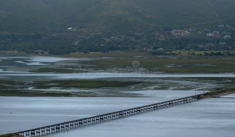 Knysna,南非:水在Knysna盐水湖的出海口,当桥梁运载的火车线跑横跨水 免版税库存图片