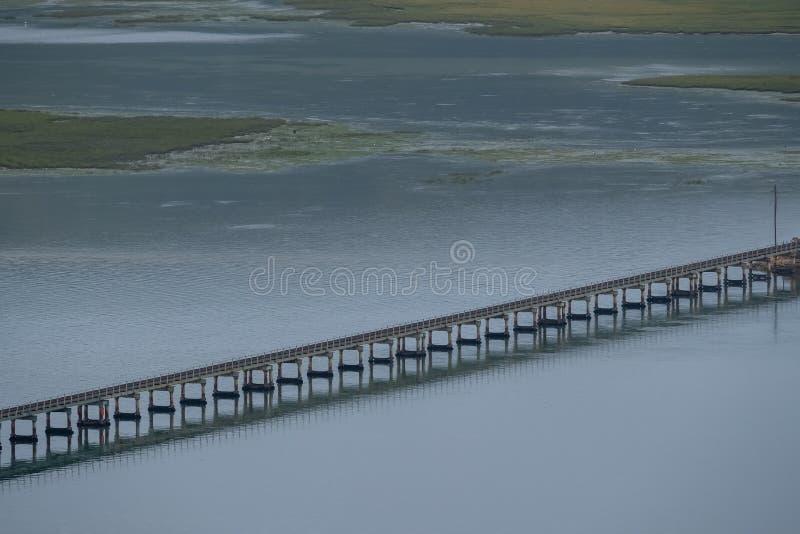 Knysna, ?frica do Sul: ?gua no estu?rio na lagoa de Knysna, com as linhas levando do trem da ponte que correm atrav?s da ?gua fotos de stock royalty free