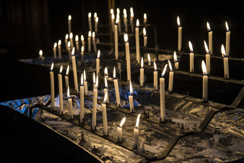 Kościelne świeczki zaświecać przeciw czarnemu tłu obraz stock