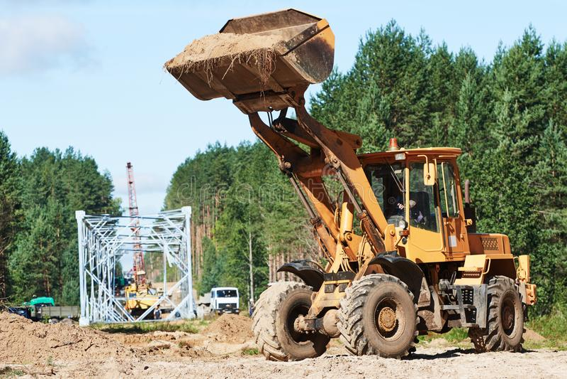 Koło ładowacza maszynowy rozładunkowy piasek przy eathmoving pracuje przy budową obraz stock