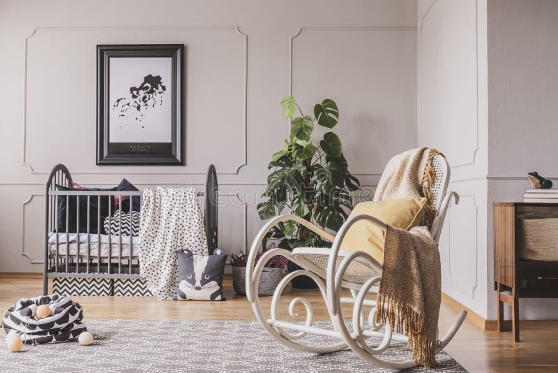 Kołysać krzesła z koc i poduszką w eleganckim dziecko pokoju fotografia royalty free