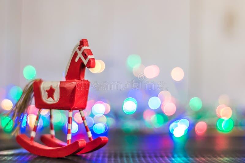 Kołysa koń z bożonarodzeniowymi światłami na drewnianym tle zdjęcia stock