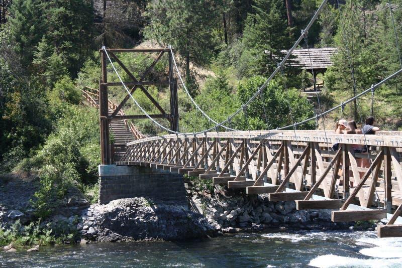 Kołyszący most przy brzeg rzeki parkiem fotografia stock